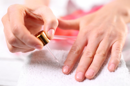 Woman paints the nails cuticle oil and nail 스톡 콘텐츠