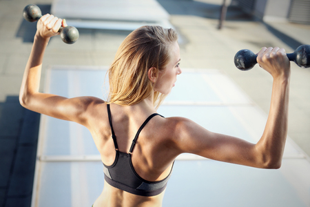 stretching condition: back muscles training with dumbbells