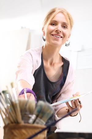 artistas: Mujer madura en el estudio de pintura Foto de archivo