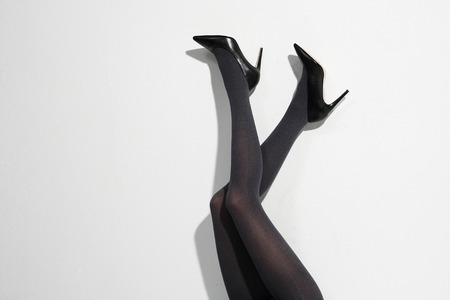 Legs and heels: Shapely female legs in high heels and black tights Stock Photo