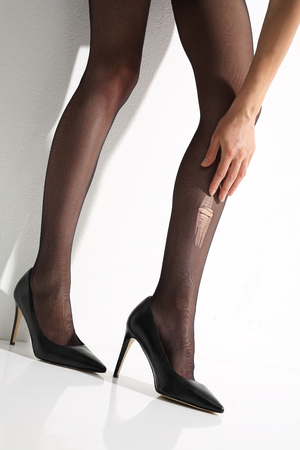 shapely legs: Wink, torn tights Stock Photo