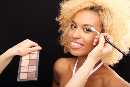 Make-up artist painting a beautiful woman eyeshadows.