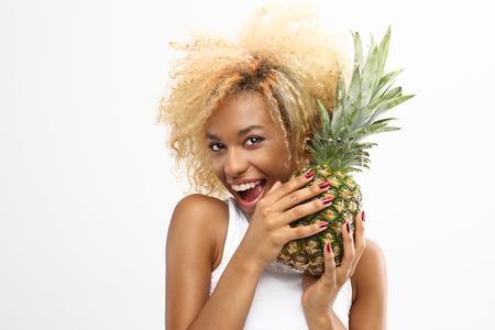 frutas divertidas: Piña centrocampista exótico en una dieta. La alegre niña de piel oscura tiene en sus manos la piña