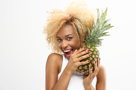 woman eating fruit: Pineapple exotic midfielder in a diet. The dark-skinned cheerful girl holds in her hands the pineapple Stock Photo