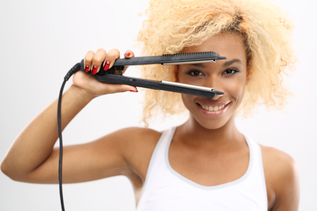 afro woman: Straighten your hair.Young girl straightens her hair with a hair straightener