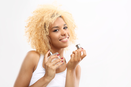 eau de toilette: Perfume, how to choose fragrance for yourself. The dark-skinned woman smelling perfume bottle