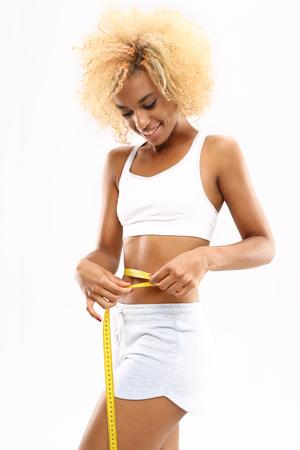 cintura: Circunferencia de la cintura. silueta esbelta. La mujer mide la cinta de medir la cintura Foto de archivo