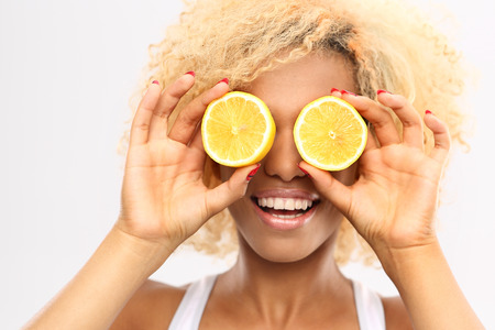 leather woman: Citrus boost of energy. Dark-skinned girl with fruits lemon Stock Photo