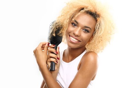 dark skinned: Tangled hair. Dark skinned young woman combs her hair brush