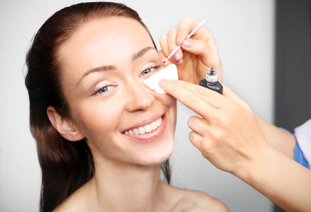 Woman during surgery eyelash extensions and permanent makeup