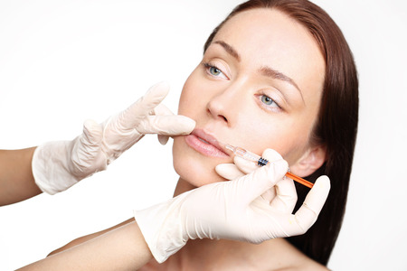 injected: Modeling mouth, aesthetic medicine. The face of a beautiful woman during the procedure of modeling the mouth, injecting