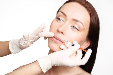 Modellierung Mund, der ästhetischen Medizin. Das Gesicht einer schönen Frau während des Verfahrens von der Modellierung der Mund, Injizieren