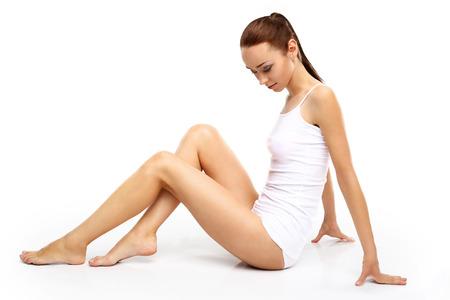 Beine einer Frau, schöne glatte Haut. Die Schönheit des weiblichen Körpers, natürliche Frau, junge Frau in weißen Dessous Standard-Bild