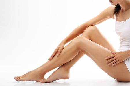 Beine einer Frau, schöne glatte Haut. Die Schönheit des weiblichen Körpers, natürliche Frau, junge Frau in weißen Dessous Lizenzfreie Bilder