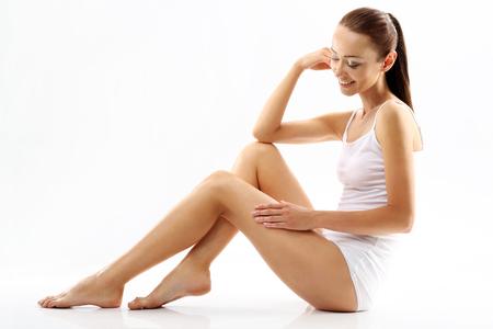 muslos: La celulitis. Una mujer revisa las estrías en las piernas Foto de archivo