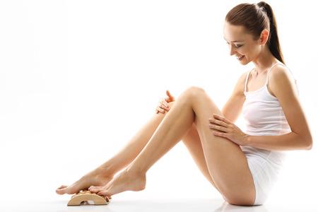 thighs: cuidado femenino. Natural, bella mujer de pie masajear masajeador de madera