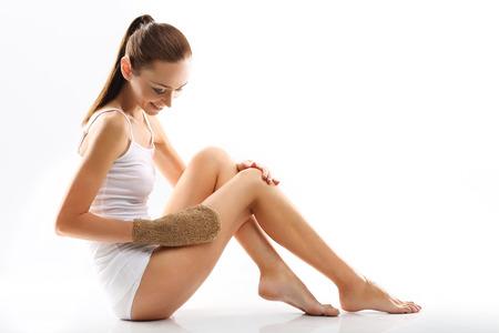 massieren: Frau massiert die Beine. Wei�e junge Frau in der wei�en W�sche massiert die F��e Massageger�t