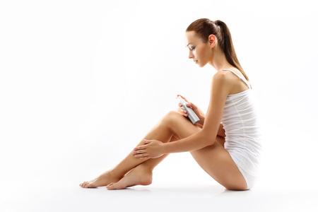 calas blancas: El cuidado del cuerpo femenino. La mujer frota en la piel de la pierna cosmética Foto de archivo