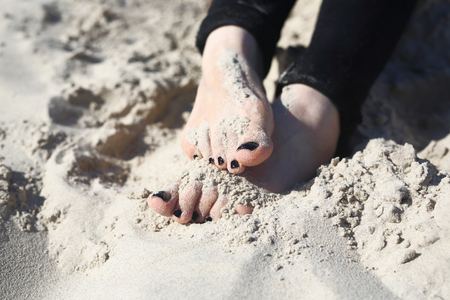 beach feet: Relax on the beach. Feet of a woman buried in sand on the beach Stock Photo