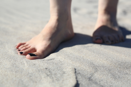 sandy feet: Beach holiday. Feet of a woman buried in sand on the beach Stock Photo