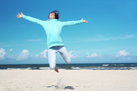 5 10 years old: Holiday! The girl jumps high on a sandy beach