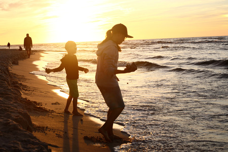 5 10 years old: Sunset over the sea. Children boy and girl playing on the sea shore on a sandy beach during sunset