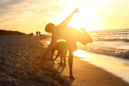 5 10 years old: Happy day. Children boy and girl playing on the sea shore on a sandy beach during sunset Stock Photo