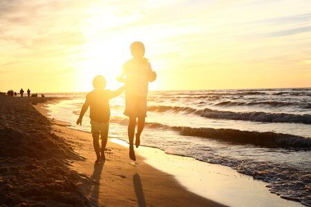 5 10 years old: Walking on the beach, sunset.Children boy and girl playing on the sea shore on a sandy beach during sunset