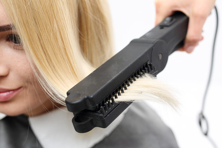 capelli lisci: Iron barbershops, hair straightening. Hairdresser hairstyle models using the straightener.