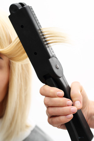 hairdressing accessories: Keratin hair straightening. Hairdresser hairstyle models using the straightener.