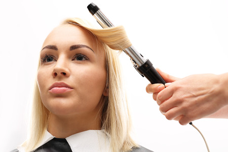 hair dryer: Hairdresser. A woman in a hair salon, barber turns hair curling iron Stock Photo