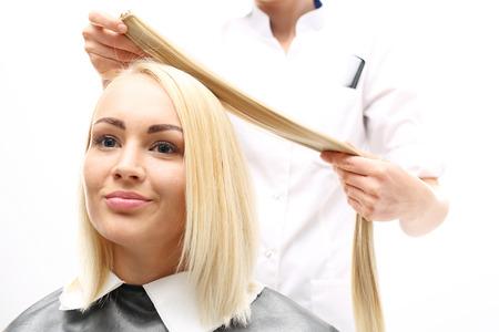 Haarverlängerung. Barber verlängert die Haare Haarsträhnen Knopf
