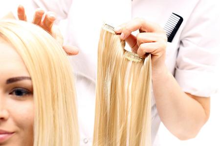 Extensions de cheveux. Barber prolonge les mèches de cheveux de boutonnage de cheveux