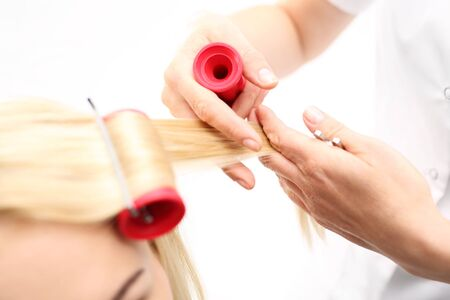 perm: Hair rollers. A woman in a hair salon, barber turns hair on rollers