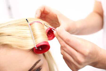 perm: Barber winds shafts, perm. A woman in a hair salon, barber turns hair on rollers