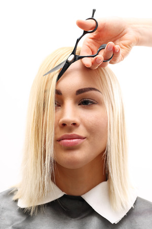 split ends: Undercutting the split ends of hair. Barber haircut woman in a hair salon Stock Photo