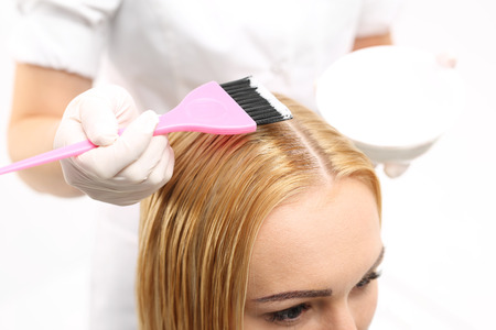 Hair dyeing. Barber hair dye is applied with a brush