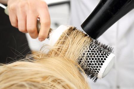 secador de pelo: Cabello seco en un cepillo redondo. Foto de archivo