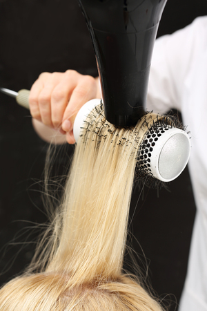 hairdressing scissors: The woman at the hairdresser, barber models hair on a round brush