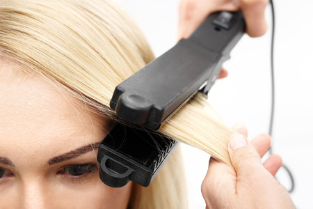 feminine beauty: Straightening. Hairdresser hairstyle models using the straightener.