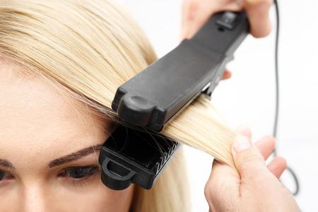 straightener: Straightening. Hairdresser hairstyle models using the straightener.