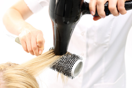 dry hair: Hairdresser dry hair. The woman at the hairdresser, barber models hair on a round brush