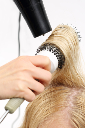 scissors hair: Styling brush. The woman at the hairdresser, barber models hair on a round brush