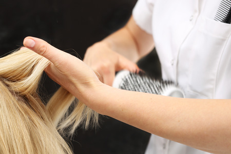 color hair: Drying hair on a round brush. The woman at the hairdresser, barber models hair on a round brush Stock Photo