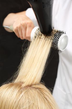Medium-length hair, hairdresser models hair brush. Stok Fotoğraf
