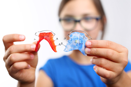 crooked teeth: Colored dental braces .Pretty girl with colored orthodontic appliance.