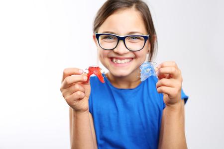 odontologa: aparato de ortodoncia. La muchacha bonita con dispositivo de ortodoncia de color. Foto de archivo