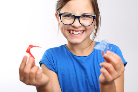 Dental braces. Pretty girl with colored orthodontic appliance.