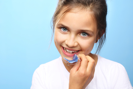 biting: Orthodontics. Portrait of a little girl with orthodontic appliance. Stock Photo