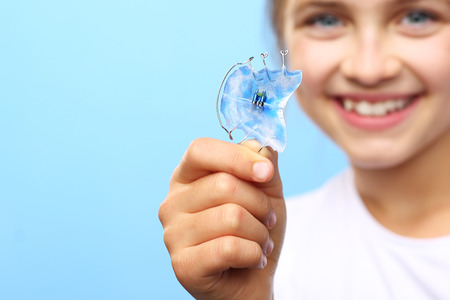 child smile: Orthodontics. Portrait of a little girl with orthodontic appliance. Stock Photo